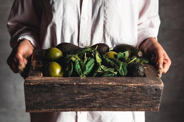 Meisje houdt een smoothie met spinazie, avocado en limoen in een vintage doos
