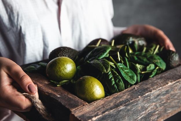 Meisje houdt een smoothie met spinazie, avocado en limoen in een vintage doos.