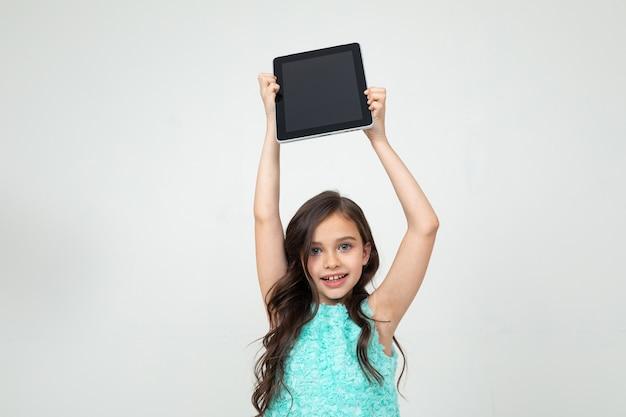Meisje houdt een tablet met een leeg scherm boven haar hoofd om een webpagina of advertentie op een witte achtergrond in te voegen.