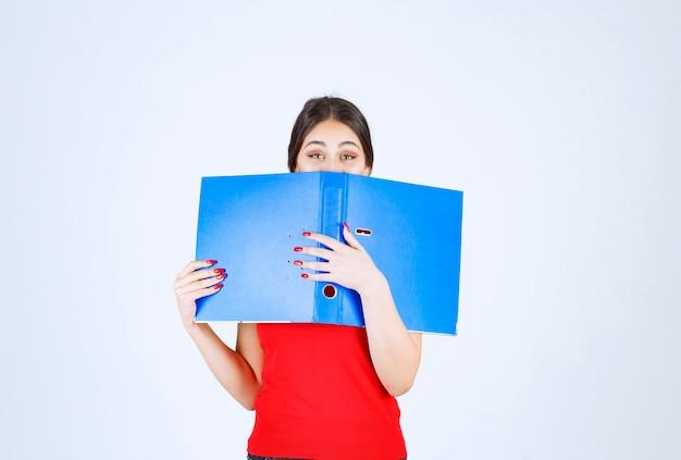 Meisje houdt en leest een blauwe map.