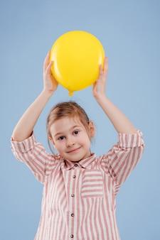 Meisje houdt gele ballon omhoog kijkt naar de camera gekleed in gestreept shirt geïsoleerd op blauwe ba...