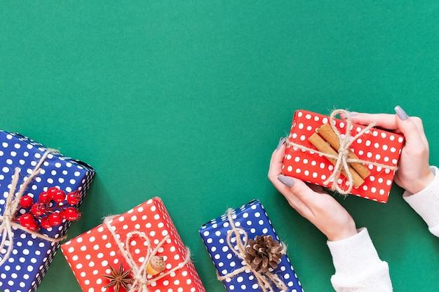 Meisje houdt geschenkdoos, rode en blauwe geschenkdozen in polka dots met kerstboomkegel en twijgen van meidoorn met eikel en kaneel op groene achtergrond, plat lag, bovenaanzicht