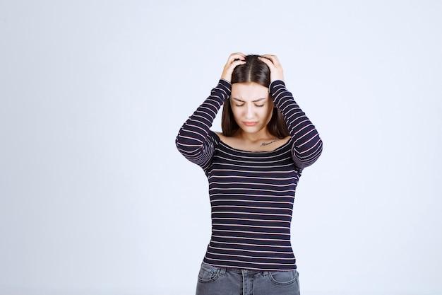 Meisje houdt haar hoofd vast als ze moe is of hoofdpijn heeft.