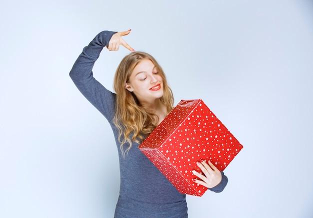 Meisje houdt haar rode geschenkdoos vast en laat het zien.