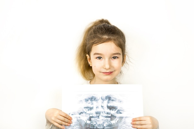 Meisje houdt haar röntgenfoto vast met een panorama van melktanden en de tweede rij verwisselbare kiezen. twee rijen tanden, wissel naar blijvende tanden. gezondheid en pediatrische tandheelkunde, orthodontie.