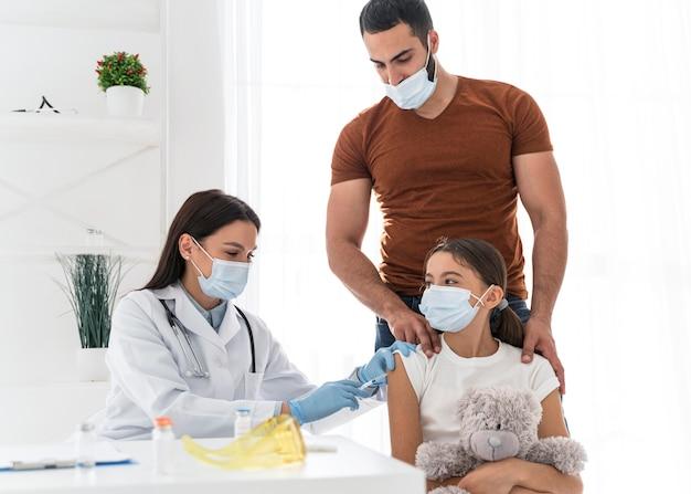 Meisje houdt haar speeltje vast terwijl ze wordt ingeënt