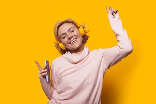 Meisje houdt haar telefoon en luistert naar muziek tijdens het dansen