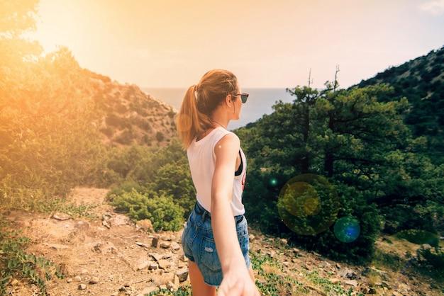Meisje houdt haar vriendje hand op vakantie op een zonnige dag