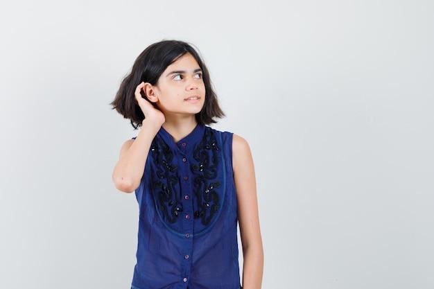 Meisje houdt hand achter oor in blauwe blouse en kijkt nieuwsgierig, vooraanzicht.