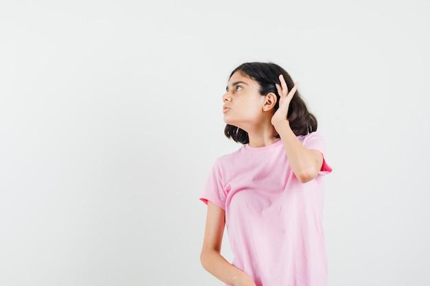 Meisje houdt hand achter oor in roze t-shirt en kijkt nieuwsgierig, vooraanzicht.