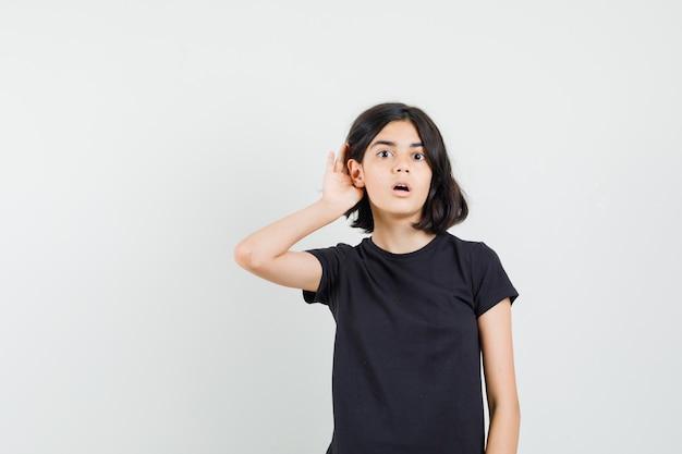 Meisje houdt hand achter oor in zwart t-shirt en kijkt nieuwsgierig, vooraanzicht.