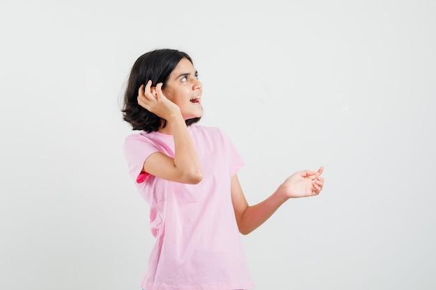 Meisje houdt hand in de buurt van oor in roze t-shirt en kijkt nieuwsgierig. vooraanzicht.