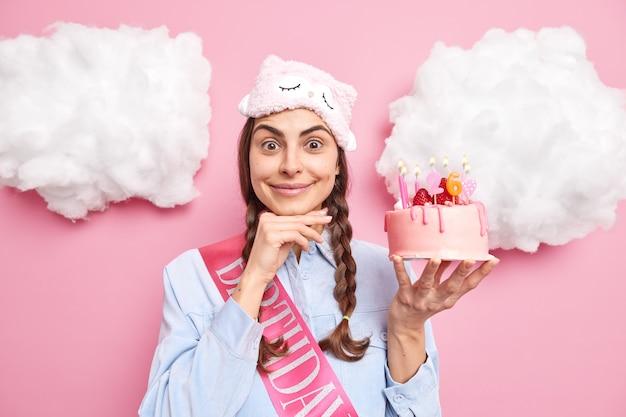 Meisje houdt hand onder kin glimlacht aangenaam draagt slaapmasker shirt en lint houdt heerlijke feestelijke cake geïsoleerd op roze