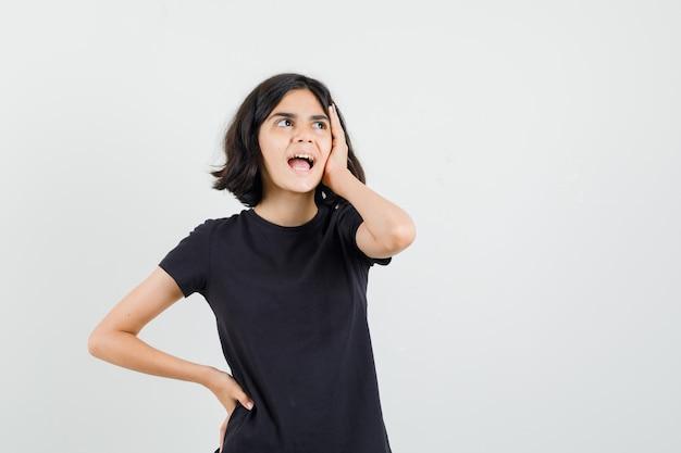 Meisje houdt hand op gezicht in zwart t-shirt en kijkt vergeetachtig, vooraanzicht.