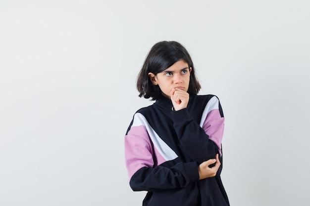 Meisje houdt hand op kin in shirt en kijkt peinzend, vooraanzicht.