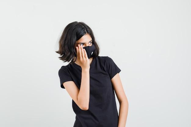 Meisje houdt hand op wang in zwart t-shirt, masker en kijkt nieuwsgierig, vooraanzicht.