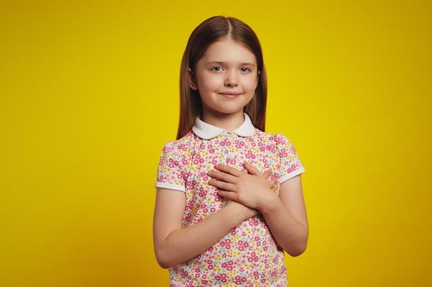 Meisje houdt handpalmen op het hart drukt waardering, plezier en dankbaarheid uit