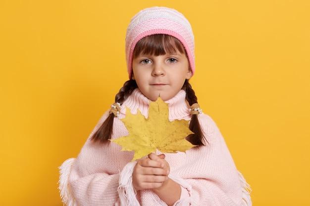 Meisje houdt herfstblad vast en kijkt direct naar de voorkant, met roze pet en poncho