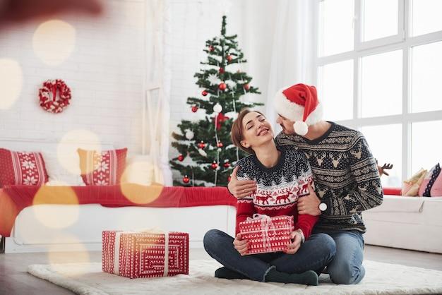 Meisje houdt kerstcadeau van haar man in de buurt van het decoratieve bed en de boom.