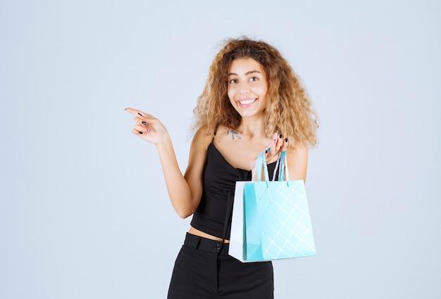 Meisje houdt kleurrijke boodschappentassen vast en wijst naar iemand anders.