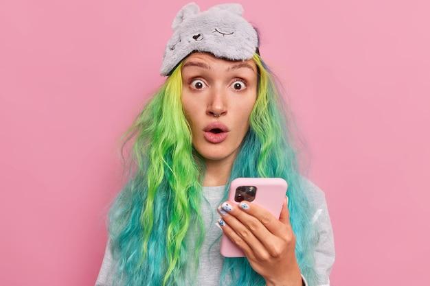 Meisje houdt mobiele telefoon vast staart afgeluisterd naar camera kan niet geloven in schokkend nieuws heeft lang haar geverfd heeft bericht op mobiel heeft verrast gezicht draagt pyjama met blinddoek