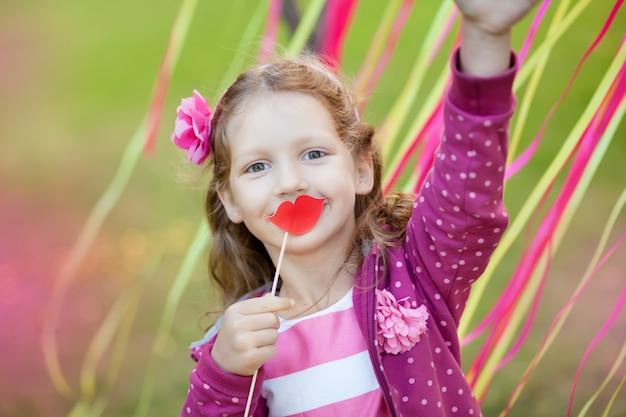 Meisje houdt papieren lippen op een stokje