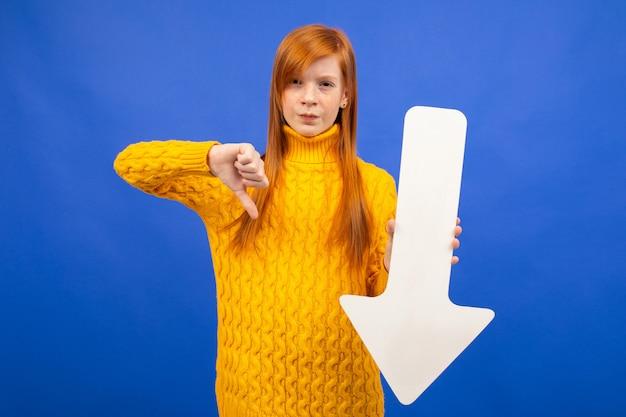 Meisje houdt pijl van papier naar beneden en toont afkeer op blauw