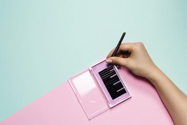 Meisje houdt pincet over een roze doos met zwarte wimpers op een pastel achtergrond. de hand van de vrouw neemt kunstmatige wimpers voor verlenging. wimper extensie concept