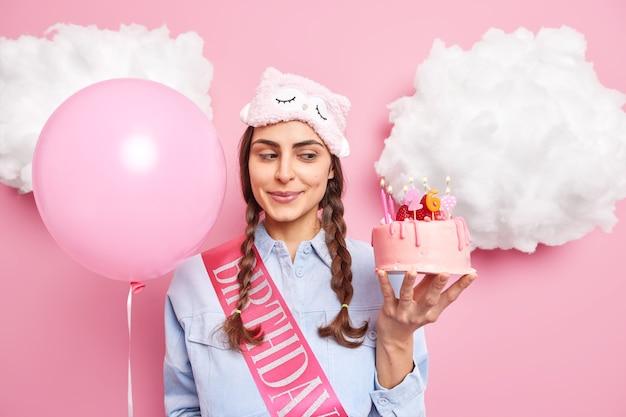Meisje houdt smakelijke feestelijke cake met brandende kaarsen opgeblazen ballon draagt slaapmasker shirt en lint geïsoleerd op roze