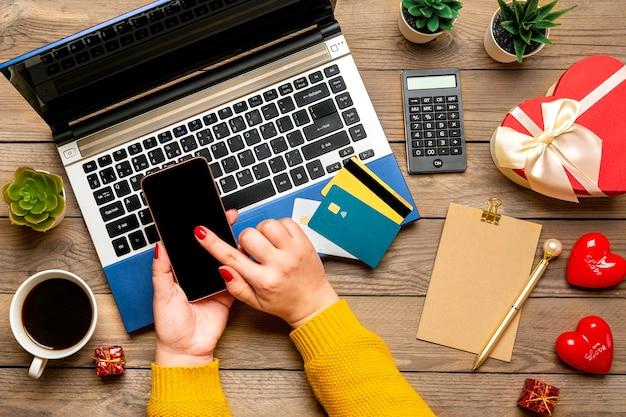 Meisje houdt smartphone, kiest cadeau, maakt aankopen, pinpas, laptop, kopje koffie