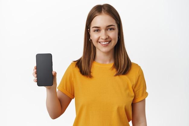 Meisje houdt smartphone vast en glimlacht, toont interface-app, leeg scherm van mobiele telefoon, staande in geel t-shirt over witte muur.