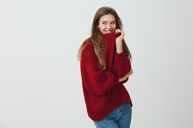 Meisje houdt van comfortabele en losse kleding. studio die van knappe charmante vrouw in rode sweater is ontsproten die kraag trekt terwijl half-gedraaide status, glimlachend en opzij kijkend met flirtende uitdrukking kijkt