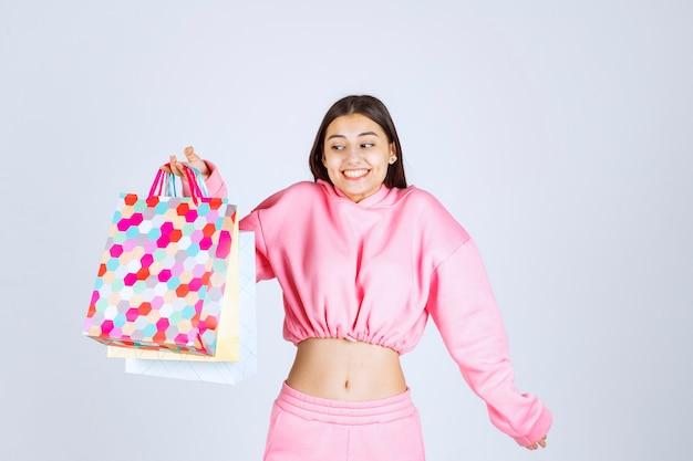 Meisje houdt van kleurrijke boodschappentassen en kijkt opgewonden.