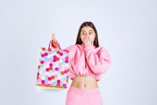 Meisje houdt van kleurrijke boodschappentassen en ziet er verbaasd uit.
