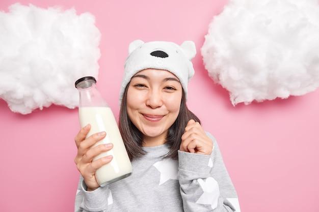 Meisje houdt van melk kan niet wachten om het te drinken gaat ontbijten na het ontwaken draagt hoed en pyjama poseert binnen op roze