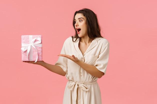 Meisje houdt van verrassingen. geamuseerde en gelukkige vrolijke jonge brunette vrouw in jurk, ontvang geschenkdoos, wijzend op dit moment onder de indruk en verbaasd als niet zo'n schattigheid verwacht, roze