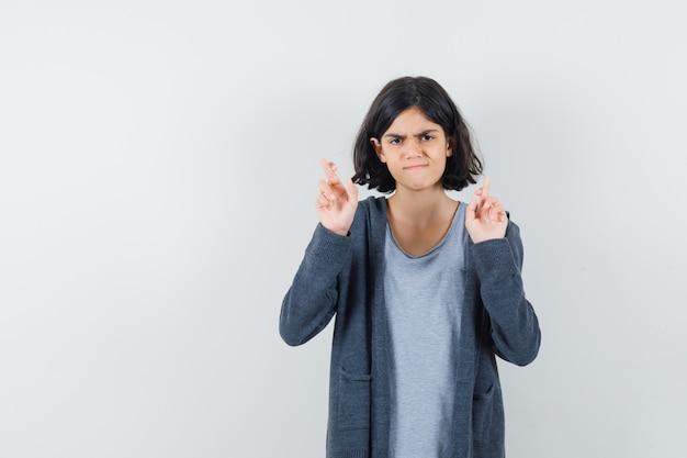 Meisje houdt vingers gekruist in t-shirt, jasje en op zoek twijfelachtig.