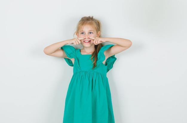 Meisje houdt vingers op haar neus in groene jurk en kijkt vrolijk. vooraanzicht.
