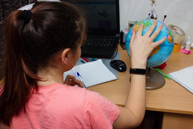 Meisje huiswerk.notebooks en globe aan de tafel. afstandsonderwijsconcept, online onderwijs.