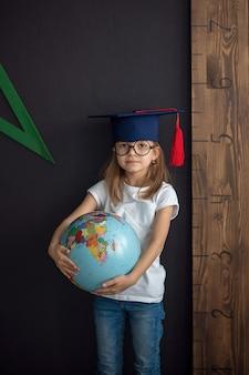 Meisje in academische hoed en ronde bril staat op de zwarte muur met wereldbol achter een liniaal, terug naar school, voorschoolse concept, kind bereidt zich voor op school