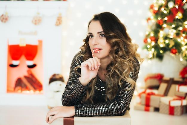Meisje in avondjurk met zuurstok voor kerstboom en open haard
