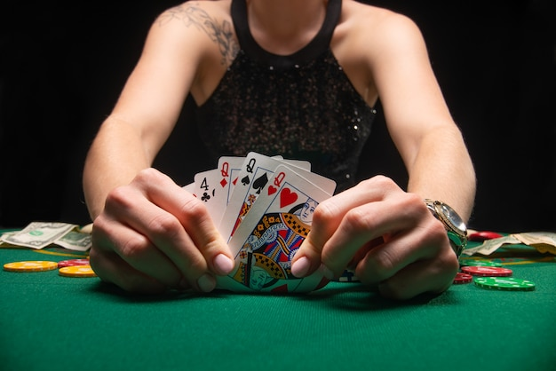 Meisje in avondjurk pokeren en kijken naar kaarten