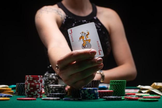 Meisje in avondjurk toont een jokerkaart