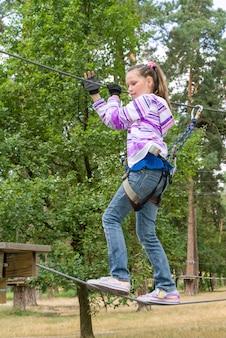 Meisje in avontuur dat hoog draadpark beklimt
