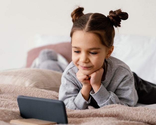 Meisje in bed kijken naar video op telefoon
