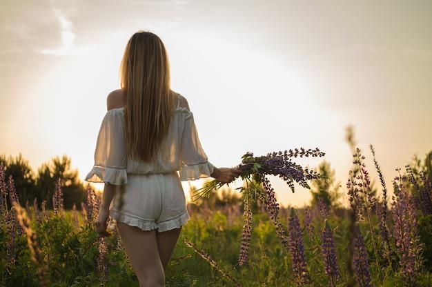 Meisje in beige algemene status op het veld met het boeket bloemen