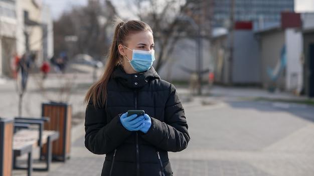 Meisje in beschermend masker en handschoenen die smartphone in openlucht gebruiken. covid 19. world coronavirus pandemie.