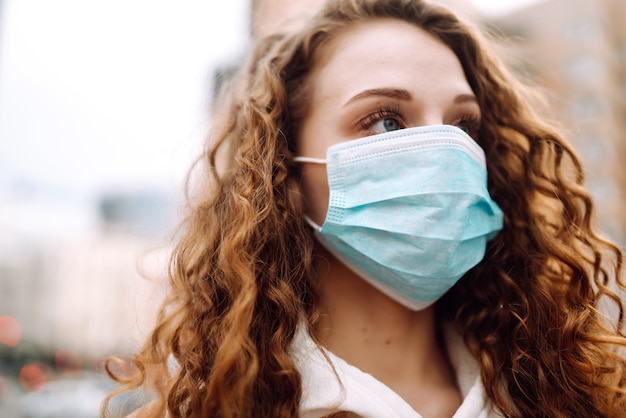 Meisje in beschermend steriel medisch masker op haar gezicht op straat