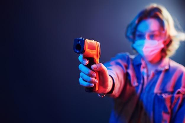 Meisje in beschermende bril en masker met infrarood thermometer. neon lichten
