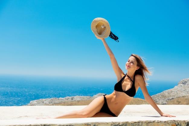 Meisje in bikini met blauwe zee en lucht